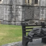 Statue of Person Sleeping on Bench